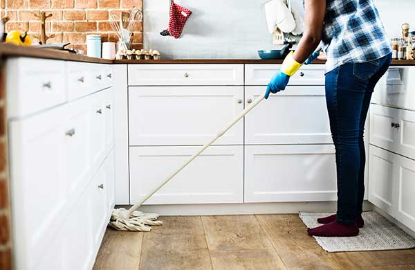 a woman engaged in properly cleaning a house for an open house showing with a mop