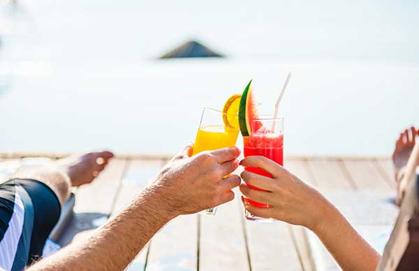 a couple finished with looking through brantford homes for sale is relaxing on a dock overlooking the ocean, giving cheers with some fruity alcoholic beverages